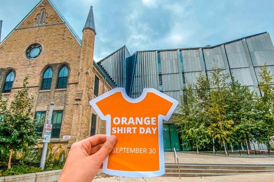 A hand holds an Orange Shirt Day sticker in front of One Spadina.